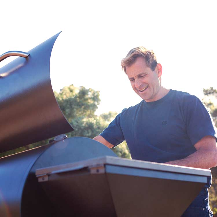 Caucasian male cooking on a Z Grills 700E Wood Pellet Smoker Grill